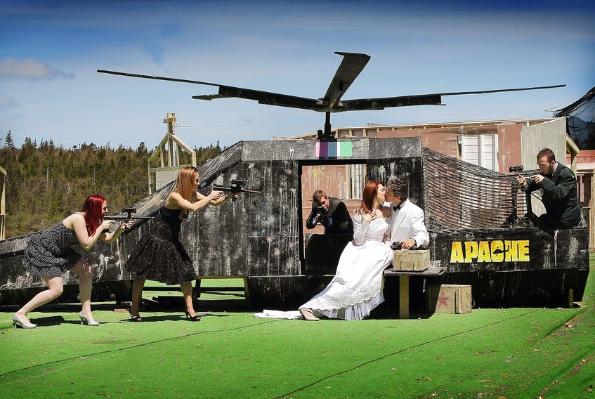 """Frontline Action co-owners Tom Davis, in the tuxedo, and his wife, Bev Moore-Davis, are """"held captive"""" near a helicopter mockup during a game of laser tag by their daughter, Jessica Moriarity, and others in happier times. With the pandemic, anyone playing at the St. John's entertainment facility has to ensure they are socially distanced or wear a face mask."""