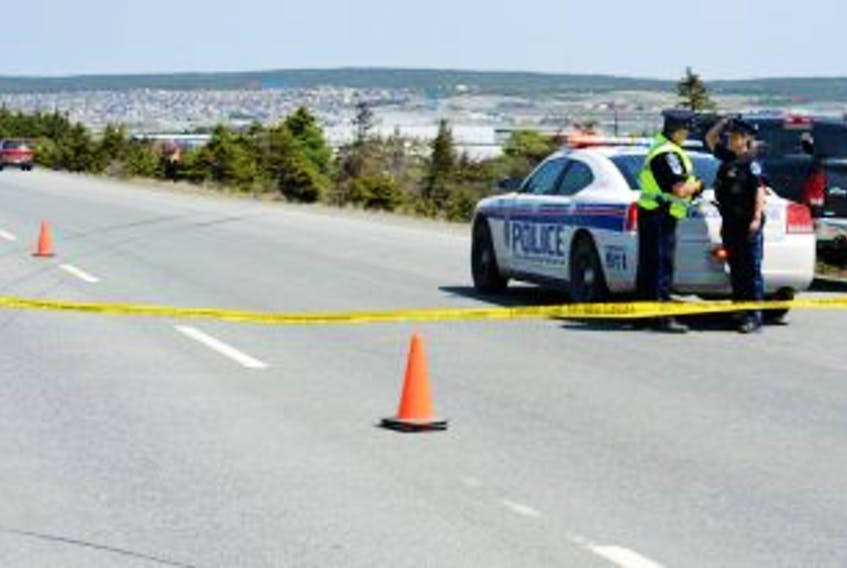 """[""""<br />Royal Newfoundland Constabulary officers Sgt. Jim Smith, left, and Const. Stephanie Carter, right, converse with one another at the scene of Sunday's serious single motor vehicle accident on the Outer Ring Road which occurred just before 11:30 a.m. The lone occupant of the vehicle – a male driver – lost control of his car and went over an embankment landing in a dense area of trees, as seen in the background. Police had the eastbound lane from the Manuel's Overpass Bridge to Donovan's Industrial Park closed to vehicle and pedestrian traffic while they conducted their investigation and removed the vehicle from the wooded area. At far left is RNC forensics identification section officer Const. Pat Hickey, photographing the accident scene as part of the investigation. The skid marks are where the vehicle operator lost control of his car and went off the road.""""]"""