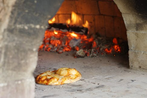 A traditional pizza is shown cooking on the wood fire of the Margaree Community Oven. After its first official season last year, a volunteer committee is looking forward to many more meals shared around the hearth by residents and families.