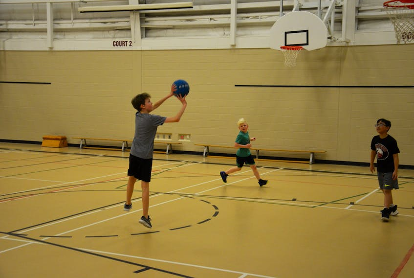Sean Borden of host Elm Street releases a shot during a recent practice in preparation for this week's Summerside Elementary Basketball League's Hoop Classic in Summerside. Koen Costain, left, and Gabe Geneson move into position for a rebound. Play begins Thursday afternoon and concludes Friday.