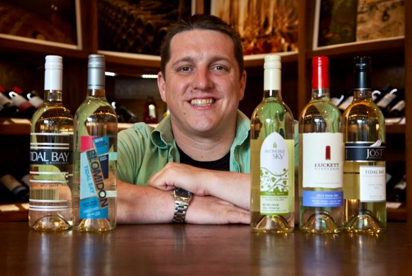 Matt Rogers, general manager of Bishops Cellar, shows of some of the Tidal Bay collection at the store June 11