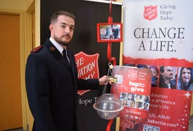 Lt. Matthew Reid making a donation using the new tiptap devices located at The Salvation Army's Christmas Kettles. The machines allow people to donate using their debit or credit card in $5 increments.