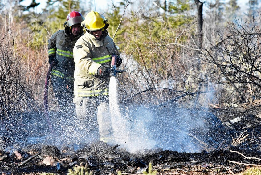 Firefighters spray water onto the ground after a March 23 brush fire on the Hardwood Hills Road on Melbourne got out of control. TINA COMEAU PHOTO
