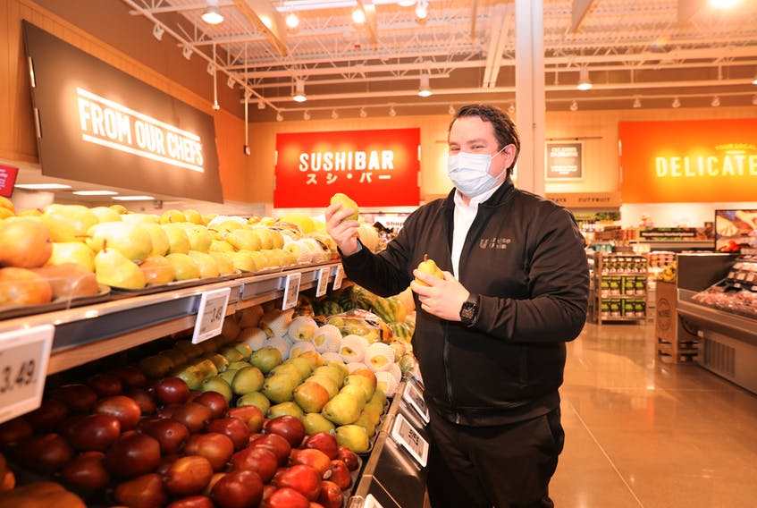 Atlantic Superstore manager Greg Bourque was thrilled to participate in the recent opening of the new Larry Uteck store. He put a few finishing touches on the produce section. - Kelly Clark Fotography