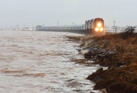 A passenger train makes its way across the marsh in Aulac, N.B. during the King Tides of 2015, when the water from the Bay of Fundy came within a centimetre of breaching the dike that is the rail line. Mike Johnson/Cumberland EMO