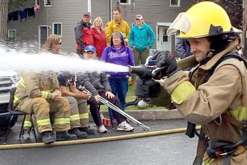 Chainse Roode, of the Truro Fire Brigade, runs the fire hose during the Walk in our Boots event held recently at the Truro Superstore parking lot.