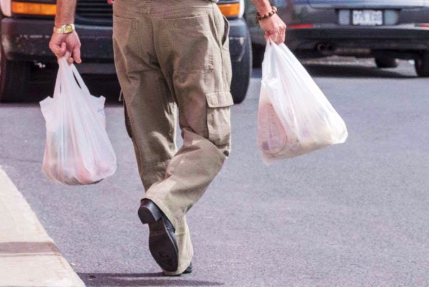 A shopper leaves a grocery store carrying his groceries in plastic bags.