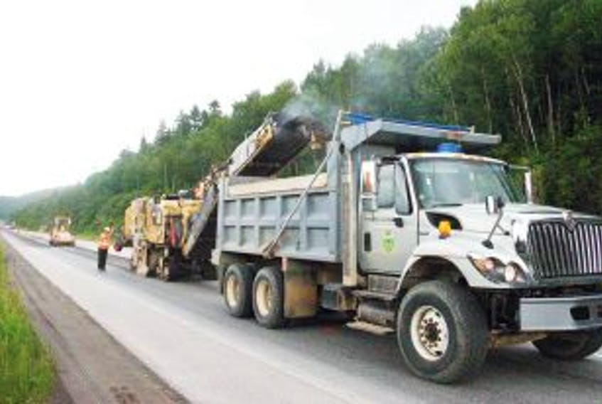 ['A paving crew works on the Trans-Canada Highway in the Humber Valley area.']