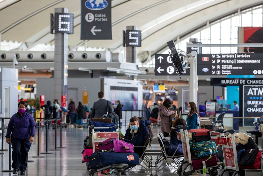 """Passengers wait for flights while wearing mandatory face masks as a """"Healthy Airport"""" initiative is launched for travel, taking into account social distancing protocols to slow the spread of the coronavirus disease (COVID-19) at Toronto Pearson International Airport in Toronto, Ontario, Canada June 23, 2020."""