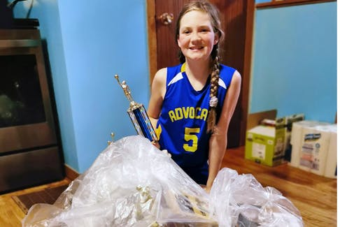 Allyson Cleveland, who plays basketball at Advocate District School, kneels by trophies and plaques she and her mother retrieved from a dumpster at the school - Ashley Collins photo