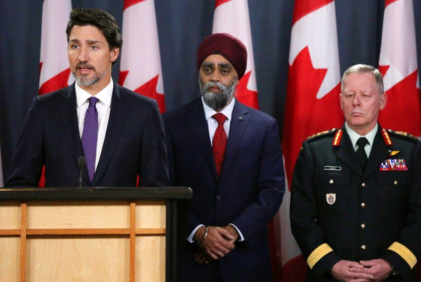 Minister of National Denfence Harjit Sajjan (C) and Chief of Defence Staff General Jonathan Vance (R) listen as Canadian Prime Minister Justin Trudeau (L) speaks during a news conference January 9, 2020 in Ottawa, Canada.