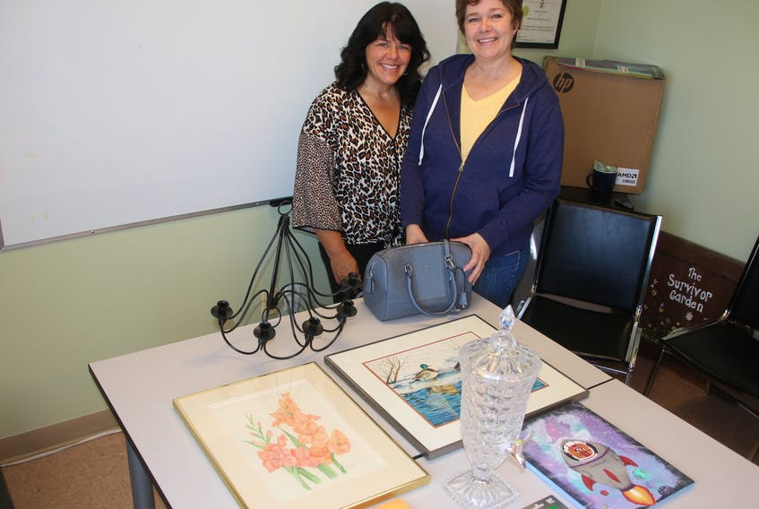 Cinda Willigar, women's support counsellor at Third Place Transition House, left, and Jackie Waugh, leader of the Heal Your Heart with Art program, are collecting items for an online auction. Funds raised will go toward the purchase of supplies for a program helping women recovering from domestic abuse. Inset is a piece of work by Waugh that will be in the auction. LYNN CURWIN/SALTWIRE NETWORK