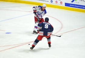 Summerside Western Capitals forward Brodie MacArthur makes a pass while being defended by the South Shore Lumberjacks' Patrick Pellerin during a Maritime Junior Hockey League regular-season game at Eastlink Arena in Summerside.