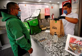 A vendor prepares food for an Uber Eats worker in Mexico City in March. Food delivery apps are fighting for East Coast market share. REUTERS/Gustavo Graf