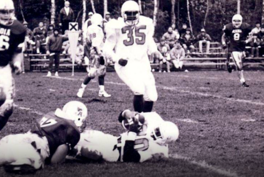 UCCB Capers player George Nimako, centre, is tackled by an Acadia Axemen player as teammate Phillip MacKenzie, right, watches during Atlantic Universities Athletics Association football action at the Canadian Coast Guard College in fall 1990. CONTRIBUTED