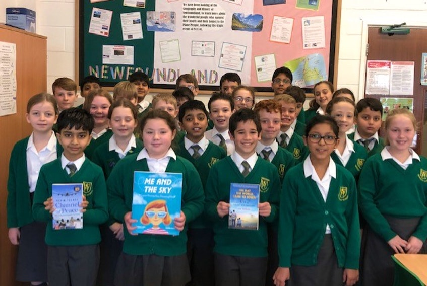 """Waverley School Year 5 and Year 6 students pose in front of a display board containing research they have done on Newfoundland and Labrador for their special project looking at the story behind the musical """"Come From Away."""" - Contributed"""