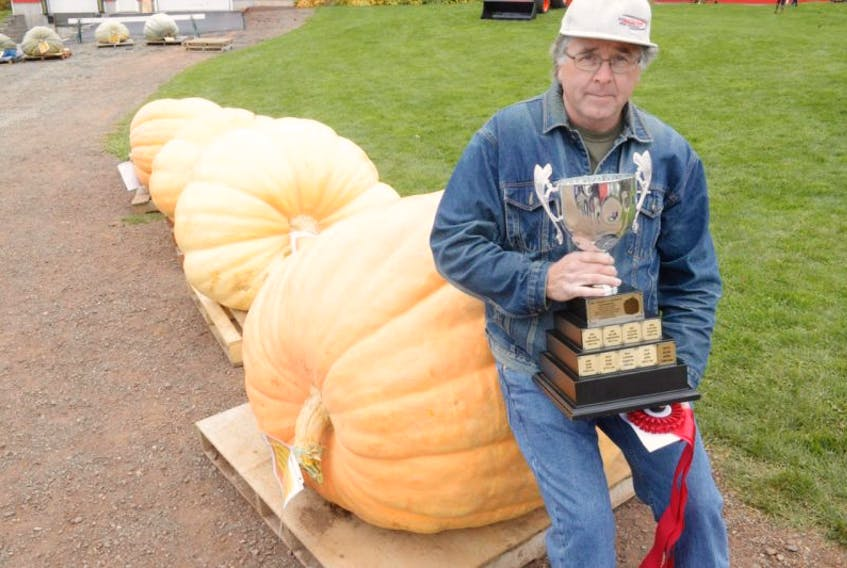 <span>Gordon Ellis stands next to his 913-pound champion giant pumpkin after the 21st annual Giant Pumpkin and Squash Weigh Off at Veseys Seeds in York Saturday.</span>