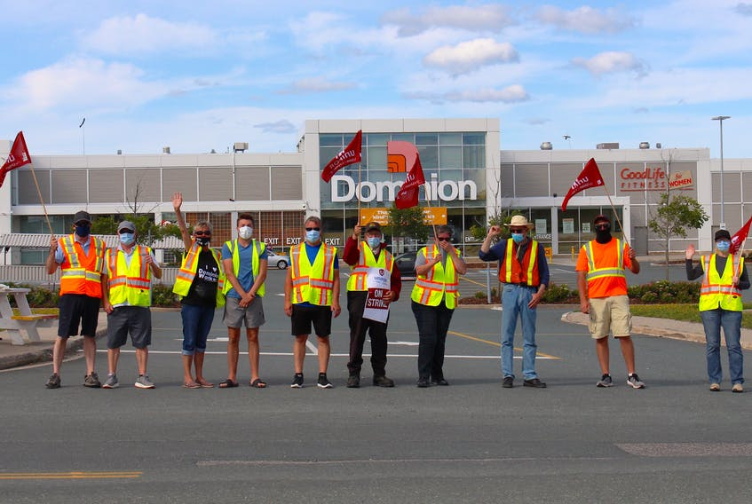 A group of Dominion employees block the entrance to the parking lot as they strike at the Blackmarsh Road location on Wednesday. Andrew Waterman/The Telegram