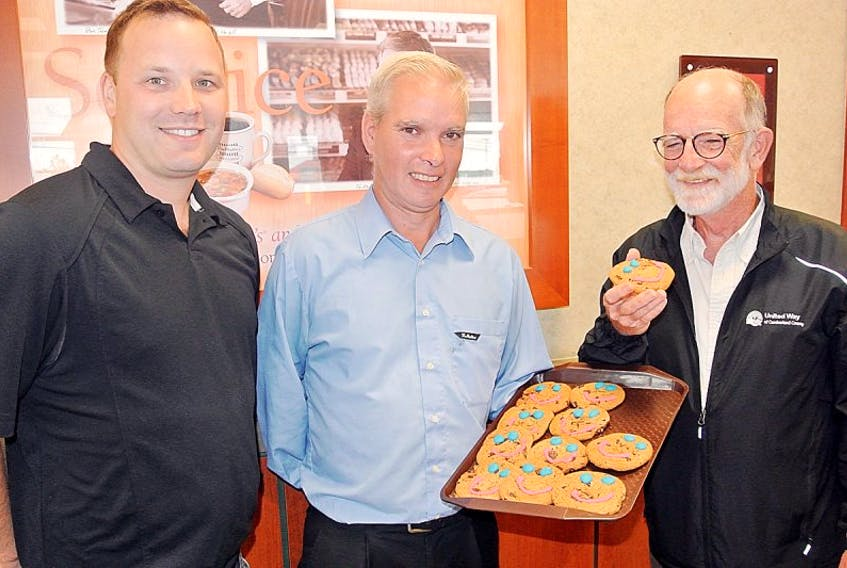 United Way of Cumberland president Curt Gunn (left) and board member Dave March (right) help Tim Hortons operations manager Lindy Marsh kick off the 2017 SMILE Cookie campaign. For $1 people can purchase a cookie at any Tim Hortons in Amherst with 100 per cent of the proceeds going to support the United Way that has set its campaign goal at $150,000.