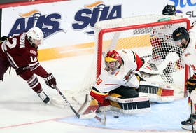 Saint Mary's Huskies' Stephen Johnson slides the puck in front of Guelph Gryphons goaltender Andrew Masters during second-period action of Thursday's University Cup quarter-final at Scotiabank Centre.   ERIC WYNNE / The Chronicle Herald