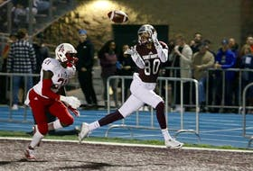 Saint Mary's Huskies receiver Lerone Robinson (80) hauls in a touchdown pass in front of Acadia Axemen defender Garvin Cius during AUS football league action on Friday night at Huskies Stadium.