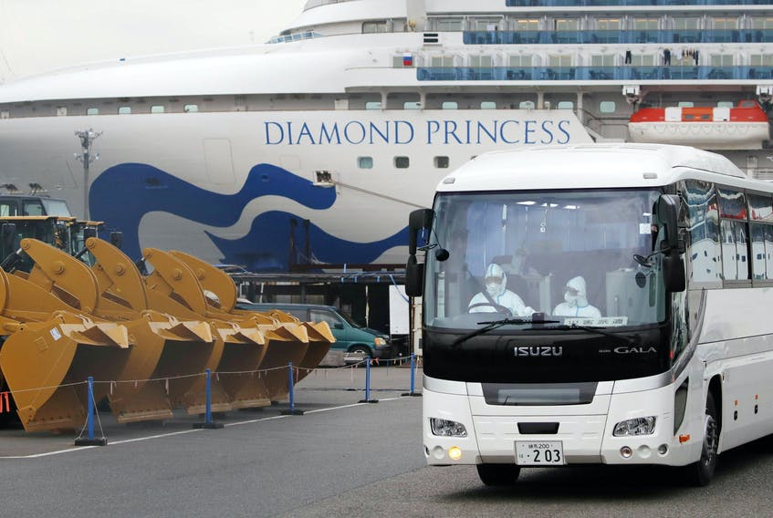 A driver wearing protective suits is seen inside a bus which believed to carry elderly passengers of the cruise ship Diamond Princess, where dozens of passengers were tested positive for coronavirus, at Daikoku Pier Cruise Terminal in Yokohama, south of Tokyo, Japan, in this photo taken Feb. 14, 2020. - Kyodo via Reuters