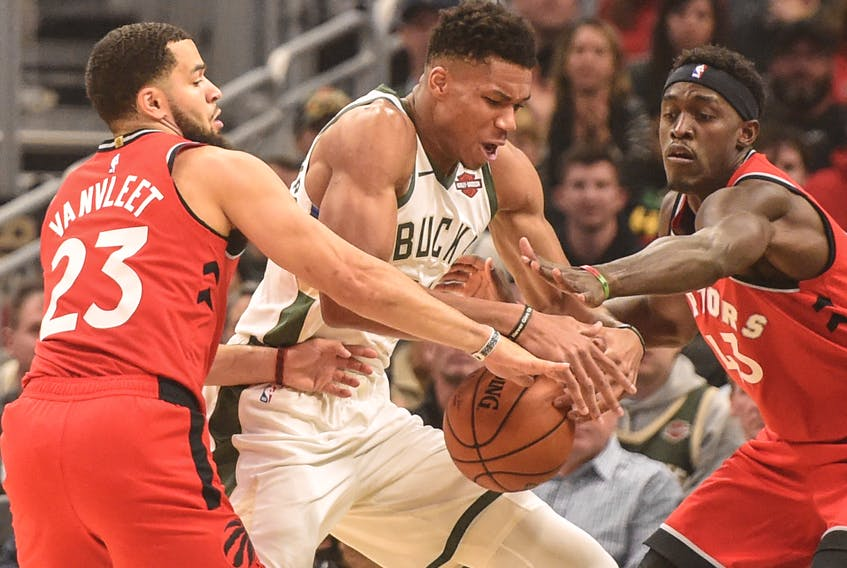 Raptors guard Fred VanVleet (left) and forward Pascal Siakam put pressure on Milwaukee Bucks forward Giannis Antetokounmpo during a game in November. (USA TODAY Sports)