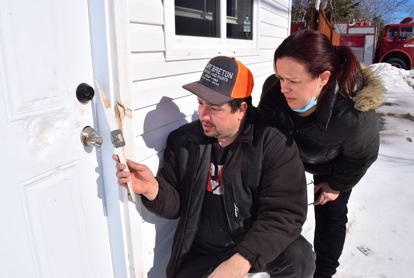 Peter Arapis, owner of PRG Diamond Sports Cards & Collectibles on Seaside Drive in Gardiner Mines, and his wife Heather Arapis, look over the damage caused by a thief who broke into the building on Sunday. Sharon Montgomery • Cape Breton Post
