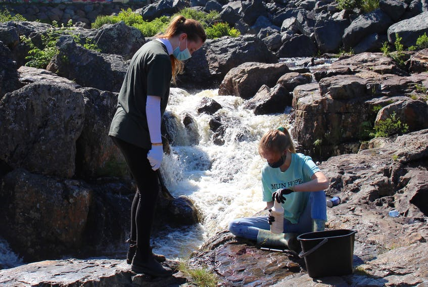 Katie Brocklehurst and Lesley Pilgrim travelled to Canyon River Trail in Manuels with the volunteer organization MUN Hope. Using water and environment friendly cleaner, the two helped each other scrub graffiti off the rocks. – Andrew Waterman/The Telegram