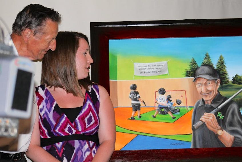 Former Summerside Boys and Girls Club employee Rachel Carter and Walter Gretzky check out the painting that was unveiled during the club's annual celebrity dinner gala as part of the celebrity golf tournament. Carter painted the image for the club's naming of the Walter Gretzky Legacy Ball Hockey Program.