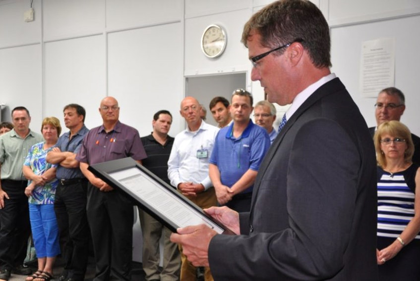 <p>Stuart MacLean, CEO of the Workers' Compensation Board of Nova Scotia, reads a letter recognizing CKF as a leader in workplace safety.&nbsp;</p>