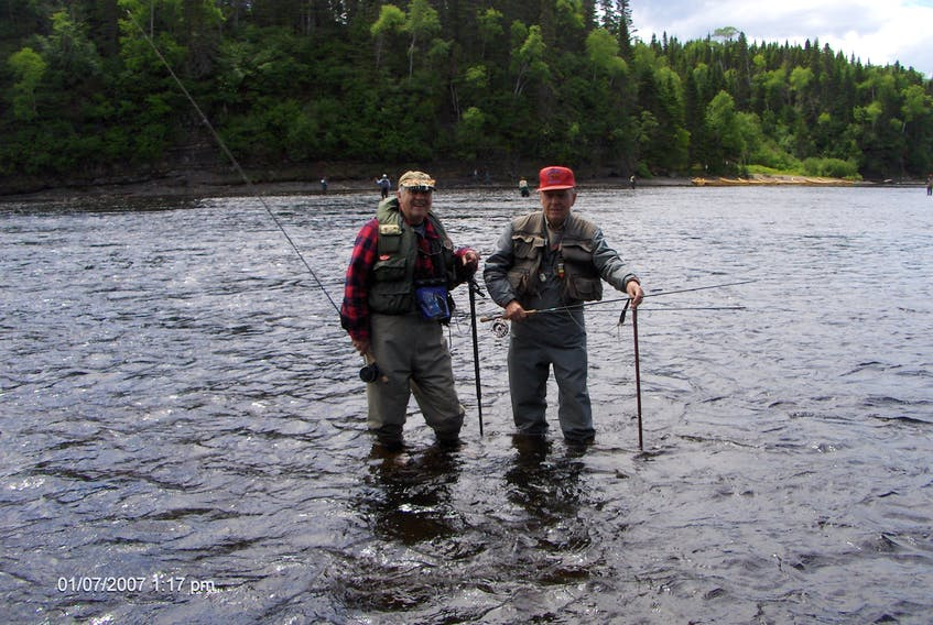 Ches Loughlin, right, and Ralph Hiscock are seen fishing together in Deer Lake Hole on the Humber River in 2015. Mr. Loughlin died in Corner Brook on Saturday.  Photo by Jeff Wells