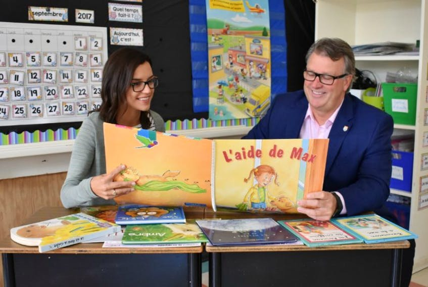 Grade 1 teacher Kellie Deacon shares a new book with Education Minister Doug Currie at West Kent Elementary School.