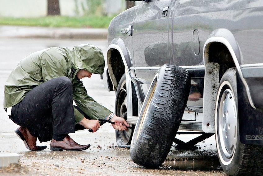 A man changes a flat tire on a rainy day in Edmonton. Jason Franson/Postmedia News files