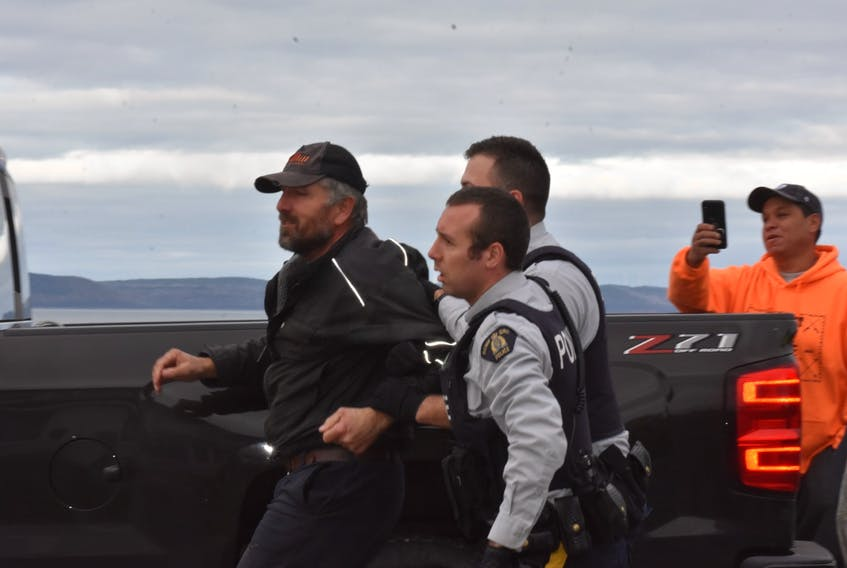 RCMP escort a man away from a confrontation over the moderate livelihood fishery on St. Mary's Bay.