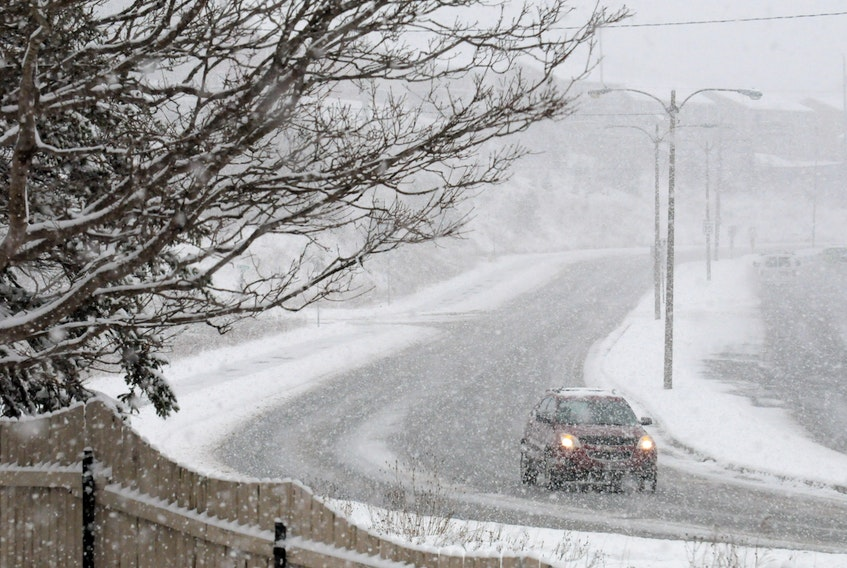 A lone motorist heads southbound on Columbus Drive as the snow falls on Friday morning amidst the mid-January snowfall. -Joe Gibbons/The Telegram