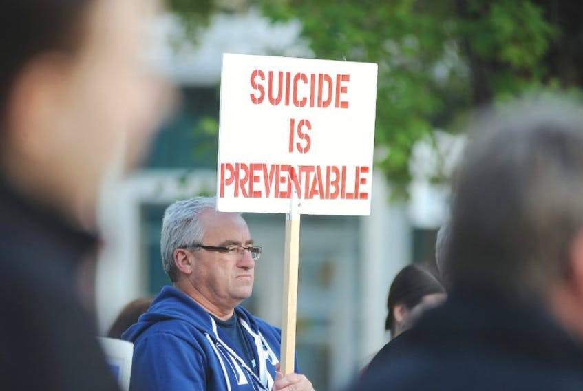 SALTWIRE FILE PHOTO: Bill Griffin holds a sign as he listens to the speakers prior to the start of the World Suicide Prevention Day walk.