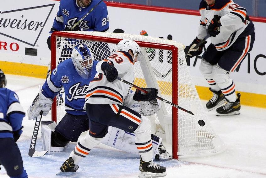 Edmonton Oilers forward Ryan Nugent-Hopkins is unable to control a bouncing puck in front of Winnipeg Jets goaltender Laurent Brossoit in Winnipeg on Jan. 24, 2021.