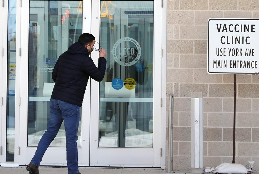 A man checks to see if he has the right doors near the COVID-19 vaccination super-site at the Winnipeg Convention Centre in Winnipeg on Sunday, Feb. 28, 2021.