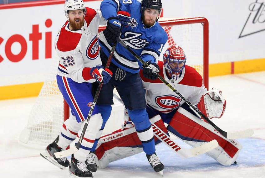 Canadiens defenceman Jeff Petry and Jets centre Pierre-Luc Dubois battle for position in front of goalie Carey Price during game Wednesday night.