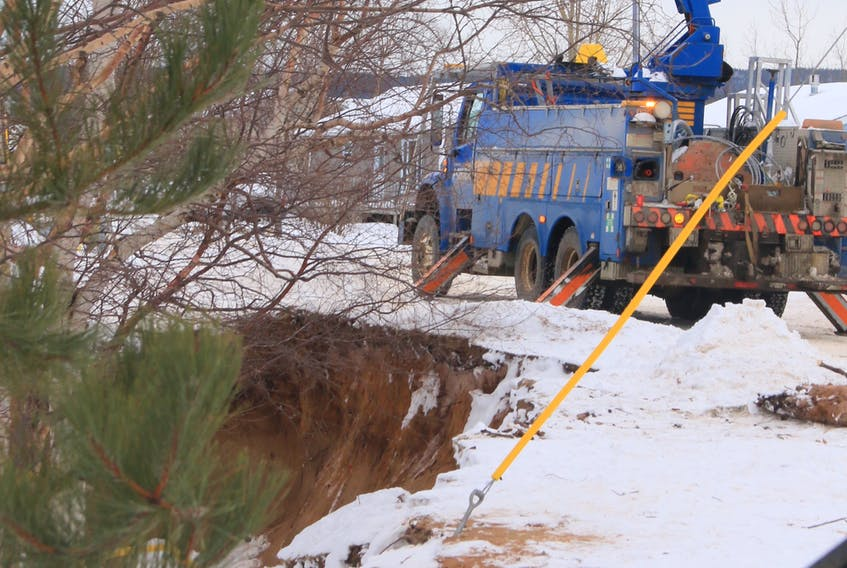 Newfoundland Power crews work to connect power lines to a pole that was moved from one side of Pine Tree Drive in Deer Lake to the other after it was compromised due to riverbank erosion.