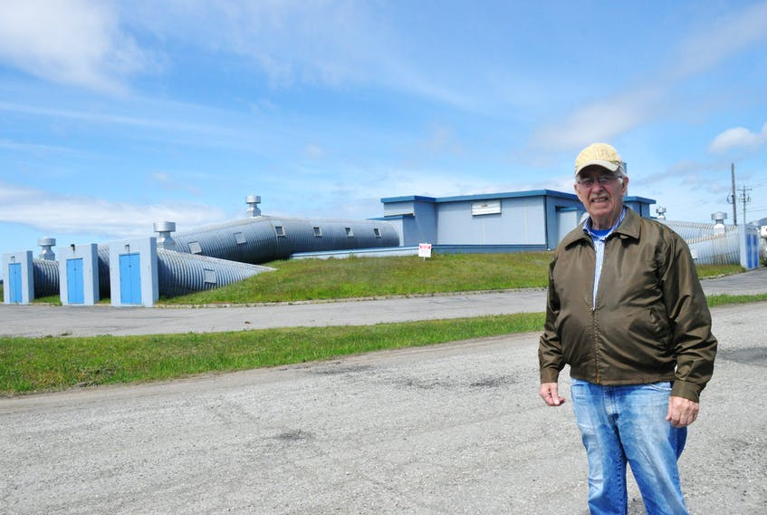 Bill Pilgrim, a former worker on the Ernest Harmon Air Force Base, poses for a photo near the Mole Hole building.