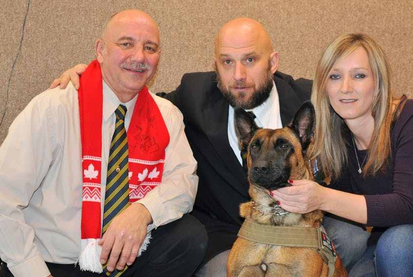 Greg Schroh, left, poses for a photo with Mike Rude, Elaine Kearney and Rude's service dog Spark after she was made an honorary lifetime member of Branch 13 of the Royal Canadian Legion in Corner Brook on Saturday.