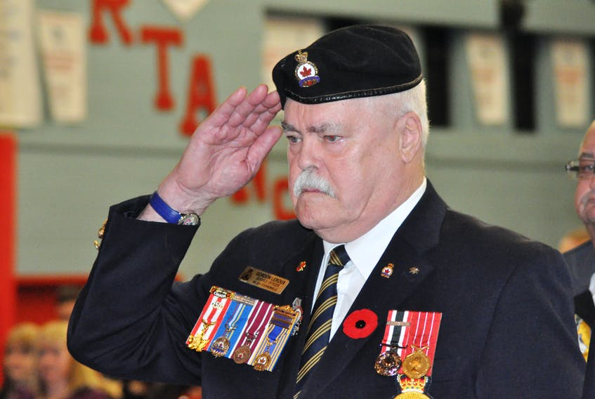 Gordon LeRoux, a former military serviceman and longtime Legionnaire, salutes the playing of the Last Post during Remembrance ceremonies at a Stephenville High School assembly Thursday.