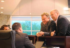 Coun. Josh Carey, left, and Coun. Tony Buckle chat with staff prior to Monday evening's public meeting of Corner Brook's city council.