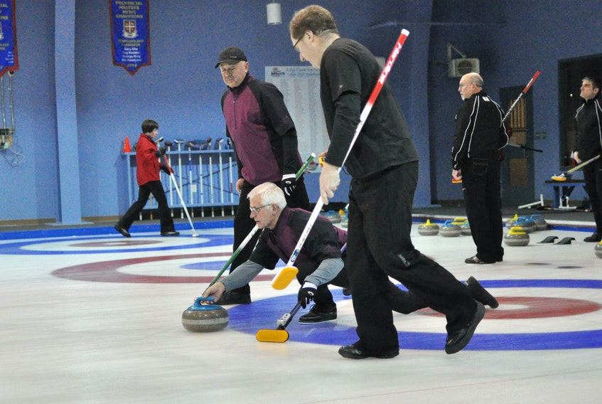 Team Oke's Blair Fradsham releases the stone while Mike Mullins, back, and Dennis Bruce get ready to sweep it towards the house during opening day action at the 2019 senior curling provincial championships at the Corner Brook Curling Club.