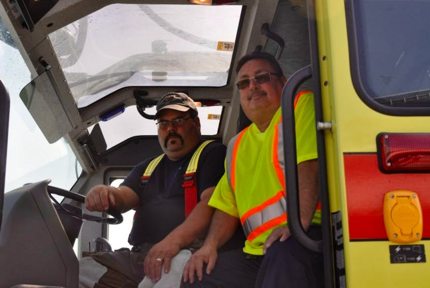Mark Cooke, left, airport technician and airport rescue firefighter, sits in the cab of one of the Deer Lake Regional Airport's rescue and firefighting vehicles with maintenance supervisor John Ryan.