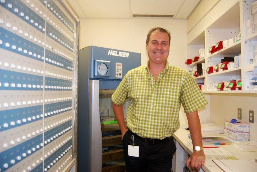 Dwayne Ballett, pharmacy manager at Sir Thomas Roddick Hospital, poses for a photo next to the current pharmacy cabinet at the hospital to be replaced by a new Pyxis medicine cabinet.