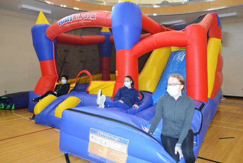 Sheldon Grant, right, of Sydney, personal trainer and wellness coach at the Frank Rudderham Family YMCA in Sydney, Janice Curnew, centre, manager of programs, and Sarah MacPherson, wellness centre team leader, relax on a big bouncy house at the YMCA Thursday, one of the items that will be up for sale during the Spring Sale at the YMCA in Sydney, Saturday from 9 a.m.-12 noon. Officials at the YMCA said they will have items from office equipment to exercise equipment and much more, their way of clearing out and refreshing the bulding before their upcoming reopening. Sharon Montgomery-Dupe/Cape Breton Post