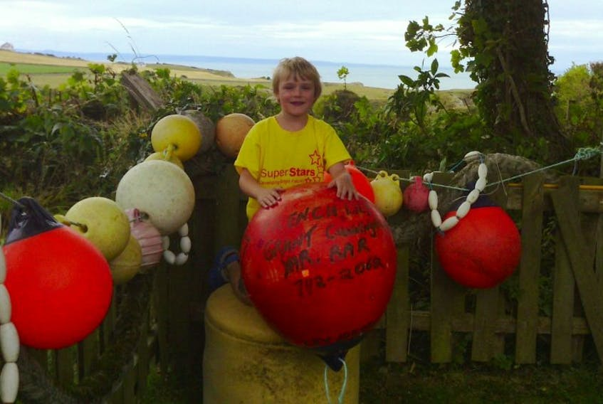 <p>Joshua Scott holds a buoy from the Yarmouth Bar that washed ashore in South Wales.</p>
